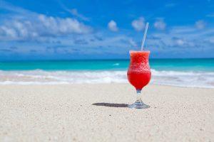 Una copa de cocktail sobre la orilla de la playa